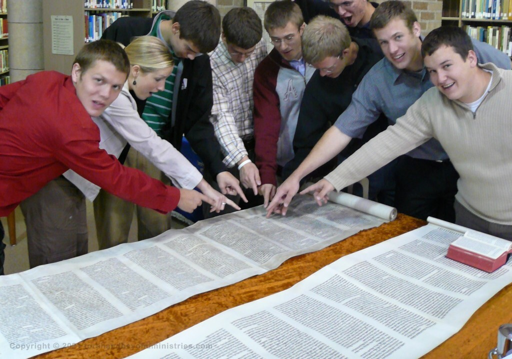 Students are pointing to Isaiah chapter 53 in the Scroll of Isaiah.