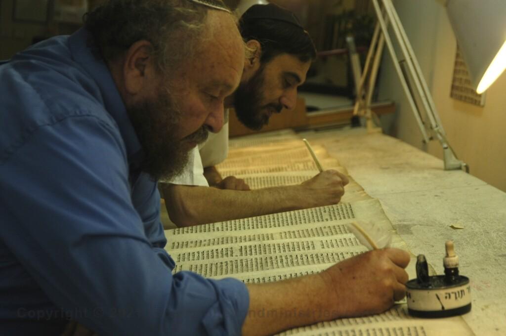 Two Soferim repairing letters on  a Torah Scroll at Macon OT in Jerusalem